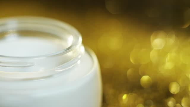 vídeos y material grabado en eventos de stock de crema de belleza dorada de alta calidad para piel sensible y rejuvenecimiento a base de ácido hialurónico gira con partículas de oro en el fondo. - descripción física