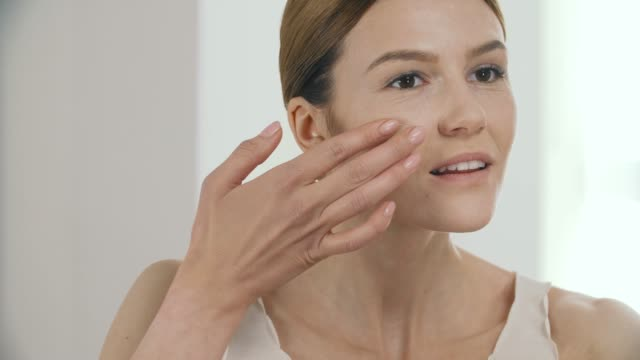 vidéos et rushes de beauté visage. belle femme application teint liquide sur la peau - image teintée