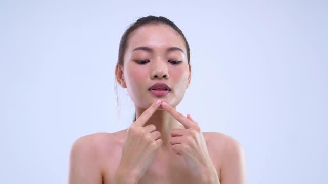 美しさの少女は彼女の顔にいくつかの化粧品を置く - 舞台化粧点の映像素材/bロール