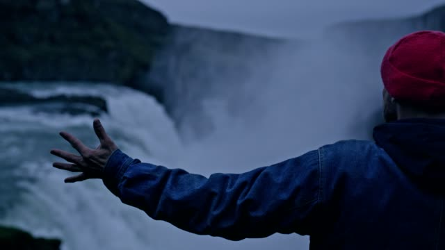 beauty in nature. traveler admiring waterfall. open arms - simbolo concettuale video stock e b–roll