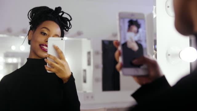 beauty model photographing its reflection in makeup mirror on mobile phone - woman mirror video stock e b–roll