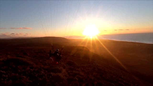 Beauty of free paragliding flying at sunset in ocean coast mountains in Morocco. Adrenaline adventure Slow motion
