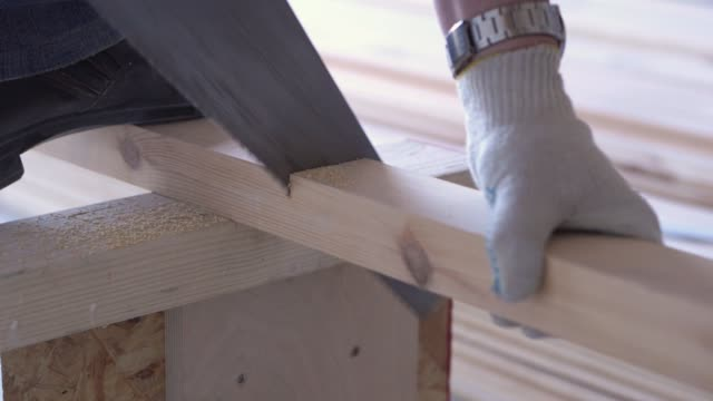 beauty of slow motion in construction and repair - construction work - a man sawing sawn wooden floor boards