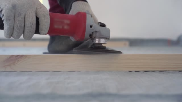 beauty of slow motion in construction and repair - master carpenter mounts pine wood floor - eco-friendly flooring. screwing lag to concrete.