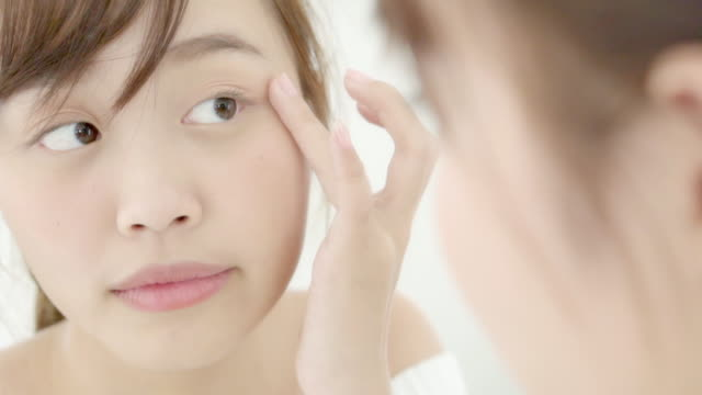 美容ポートレート若いアジアの女性は、寝室でウェルネスとスキンケア白人をチェックの鏡を見て、健康、ライフスタイルと幸福の概念のための美しい女の子の幸せな顔。 - スキンケア点の映像素材/bロール