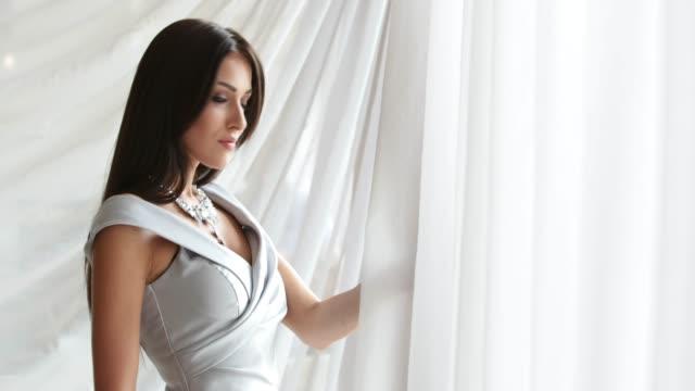 stockvideo's en b-roll-footage met schoonheidskoningin model in mouwloos grijze jurk en halsketting - halsketting