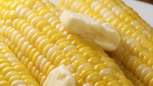 Beauty shot of fresh cooked corn topped with melting butter.