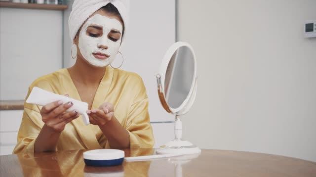 skönhet, hudvård och folks koncept. leende ung kvinna. applicera masken i ansiktet och medan du tittar på spegeln och applicera handkräm. - japanese bath woman bildbanksvideor och videomaterial från bakom kulisserna