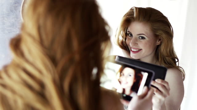 Beauty tablet mirror   GL Slow motion dolly video clip of a very beautiful woman taking a self-video, in a mirror whilst preening & smiling. vanity stock videos & royalty-free footage