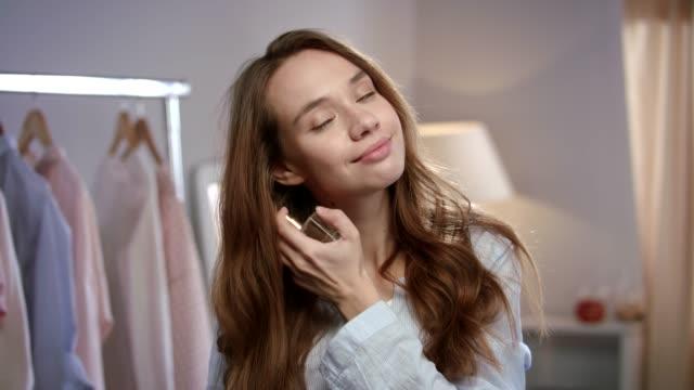 vídeos de stock e filmes b-roll de beauty woman apply perfume on body. portrait of brunette woman enjoy essence - perfume