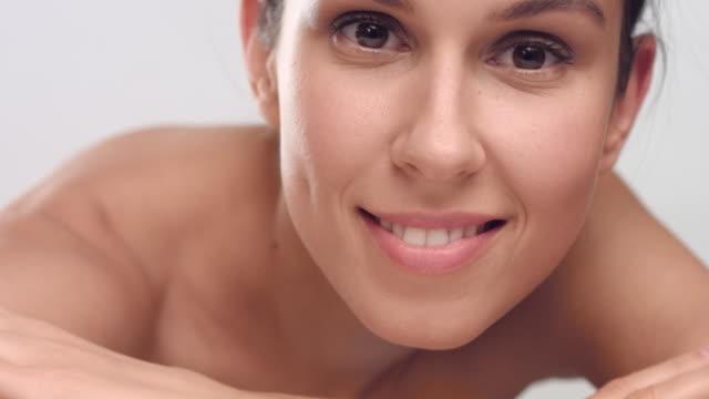 beauty woman looks at the camera and smiles - viziarsi video stock e b–roll