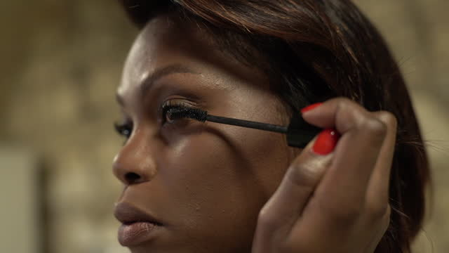 vidéos et rushes de verticale de femme de beauté appliquant le maquillage sur des cils. noir américain. - mascara