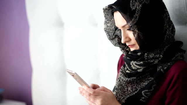 beauty young arabic woman using her smartphone - abbigliamento modesto video stock e b–roll