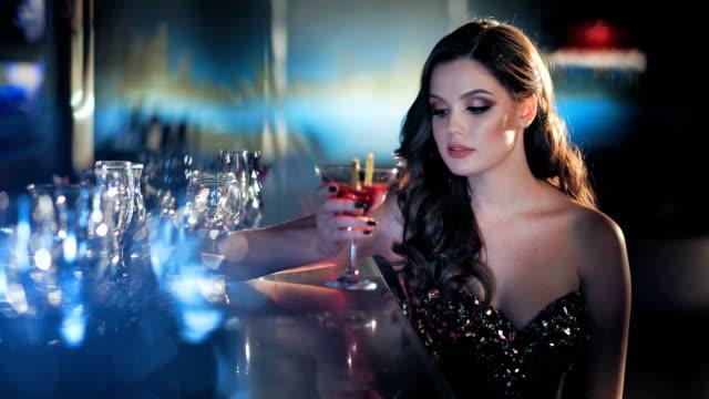 美容高級インテリアでワインのグラスとバーで座っている若いブルネットの女性 ビデオ
