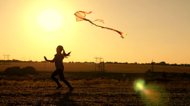 Beauty young girl running with kite at sunset