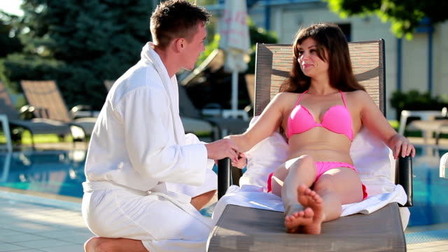 Beauutiful brunette sunbathing on the deck chair and talking with her boyfriend