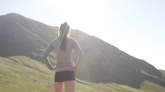 Become the better version of you everyday 4k video footage of a young woman admiring the view from a mountain top after her run arms akimbo stock videos & royalty-free footage