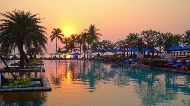 bed pool and umbrella around swimming pool with sunset or sunrise sky - vídeo