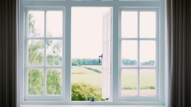 vídeos de stock, filmes e b-roll de cortinas do quarto fechando em vista da paisagem através da janela - janela