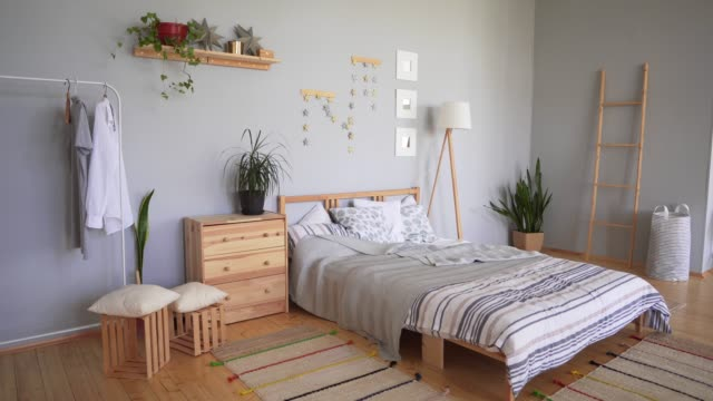 vídeos de stock e filmes b-roll de bedroom set with cozy accessories in the scandinavian style. a bed with a large number of pillows, soft carpets and blankets. - hygge