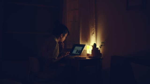bedtime : asian woman working at home overtime at night - surfować po internecie filmów i materiałów b-roll