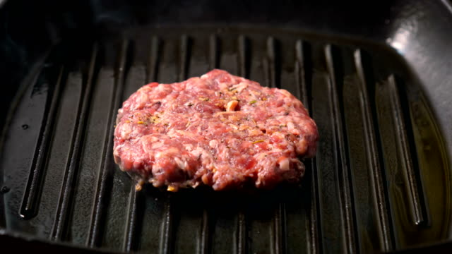 Beef burger patties grilling on a griddle pan - vídeo