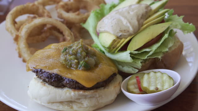 Beef cajun cheese burger with avocado and onion rings side Beef cajun cheese burger with avocado and onion rings side onion ring stock videos & royalty-free footage