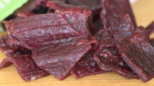 Beef jerky close up Beef jerky close up over a wooden table jerky stock videos & royalty-free footage
