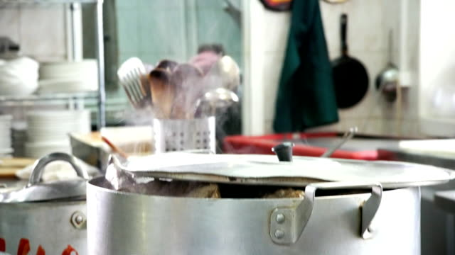 Beef meat boiling and utensils hanging on holder in the kitchen video