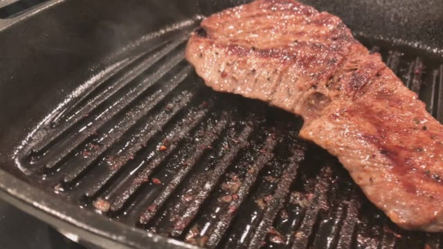 Beef Sirloin Steak Meat Cooked over an Open Stovetop Gas Flame on Cast Iron