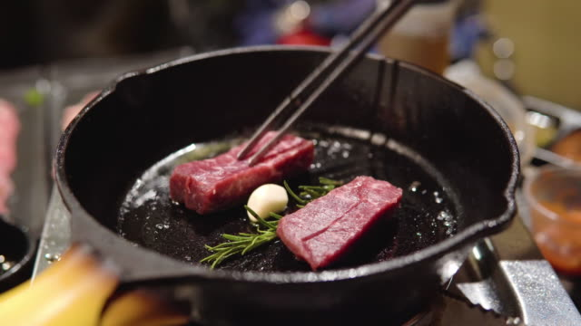beef steak in a cast iron skillet. - сковорода стоковые видео и кадры b-roll