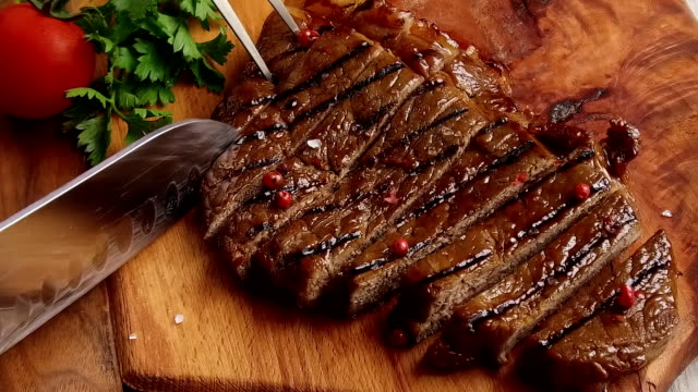 Beef steak on the board cut with a knife slow motion video