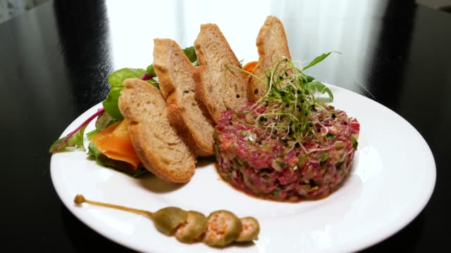 Beef tartar with capers. Beef tartar with slices of bread. Beef tartar with slices of bread. Raw meat tartare for gourmet meat. ground beef stock videos & royalty-free footage