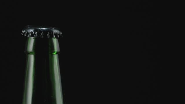 beer bottle on black background closeup.