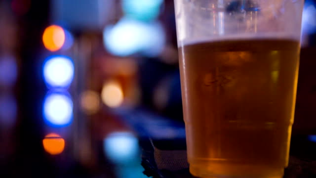 Beer Cup Pick Up at Bar Close Up a plastic beer cup is on a bar napkin and a hand picks it up and places it down. Focus on beer cup gripping stock videos & royalty-free footage