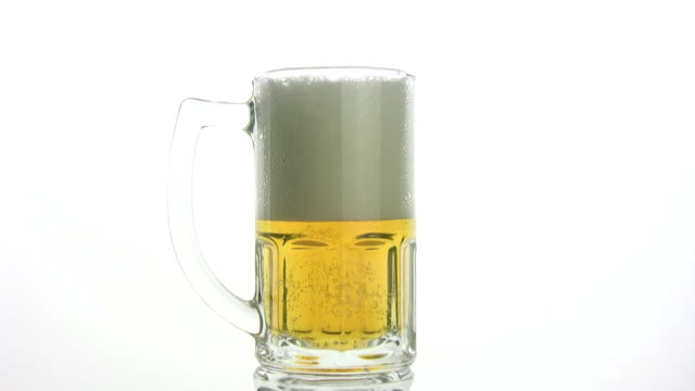 Beer foam Beer foam quickly settles in a beer mug. Timelapse. A white background. stuffed stock videos & royalty-free footage