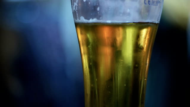 Beer Glass in a Pub. Half drunk glass of beer with an out of focus people on background. Pint glass of lager on pub table picked up and put down lager stock videos & royalty-free footage