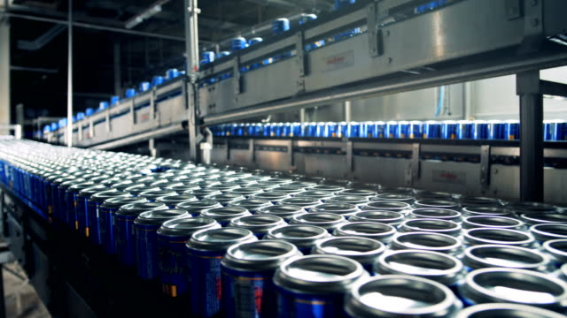 Beer in cans moving on a conveyor at a brewery, close up.