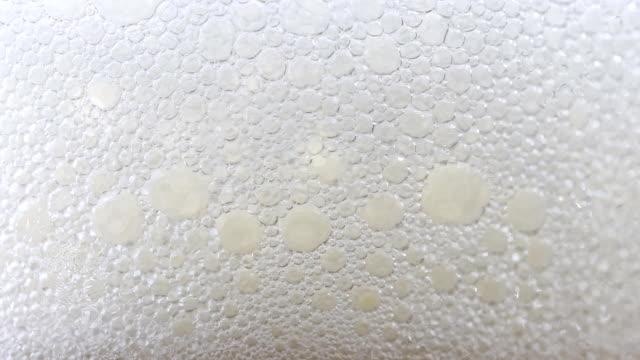 vídeos de stock e filmes b-roll de beer in drinking glass close-up - bebida com espuma