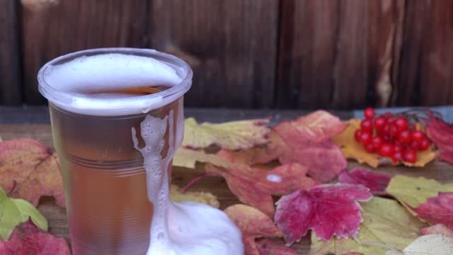 beer is poured into a glass. beer froth pours over the rim of the mug. low alcohol drink. dry autumn leaves on the table, wooden background. October folk festivals, Oktoberfest. International Beer Day