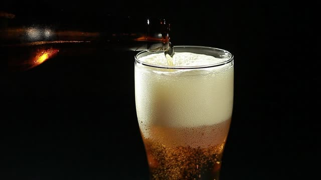 Beer is poured into a glass from a bottle on a black background