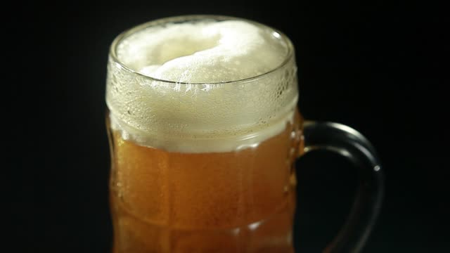 Beer is poured into a glass on a black background close up Beer is poured into a glass on a black background lager stock videos & royalty-free footage