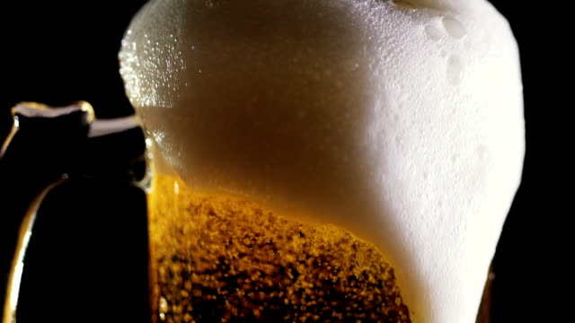 Beer is poured into a mug in a bar. Close-up - video