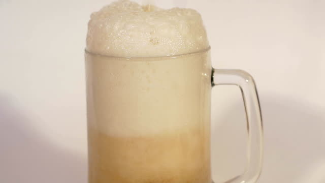 Beer is pouring from the top into glass, slow mo. video