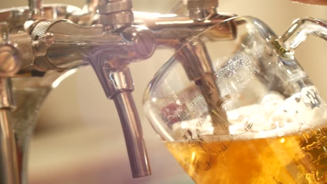 beer is pouring from the top into the glass forming waves - birra video stock e b–roll