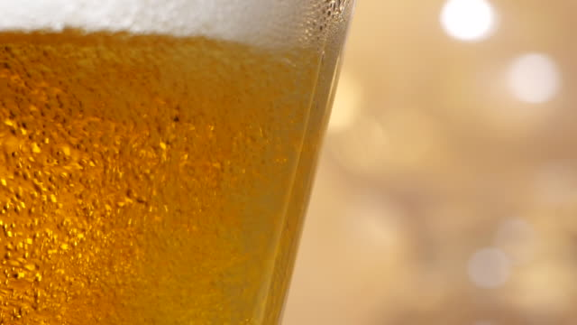 vídeos de stock e filmes b-roll de beer is pouring into a glass with foam bubbles in slow motion - lager