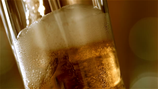 Beer is pouring into the glass. Closeup. Beer poured into glass. Glass is angled and we see it from the side. Close up of the top of the glass. HD Slowmotion. Extreme closeup. Macro. lager stock videos & royalty-free footage
