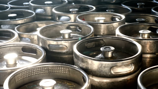 beer kegs in sunlight stand together in brewery. steel barrels in a wholesale warehouse ready for shipment. 4k - acciaio inossidabile video stock e b–roll