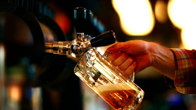 Beer on a tap. Closeup side view of unrecognizable bartender pouring beer from a tap at a beer house. 4k bar counter stock videos & royalty-free footage