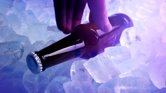 vídeos de stock, filmes e b-roll de a cerveja pegou do gelo em luzes do clube - clubbing